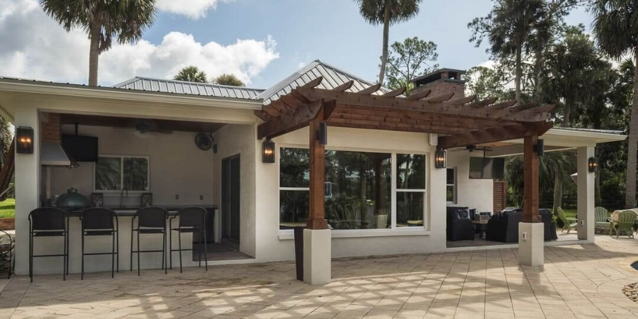 Backyard of custom Florida home with outdoor bar and pergola