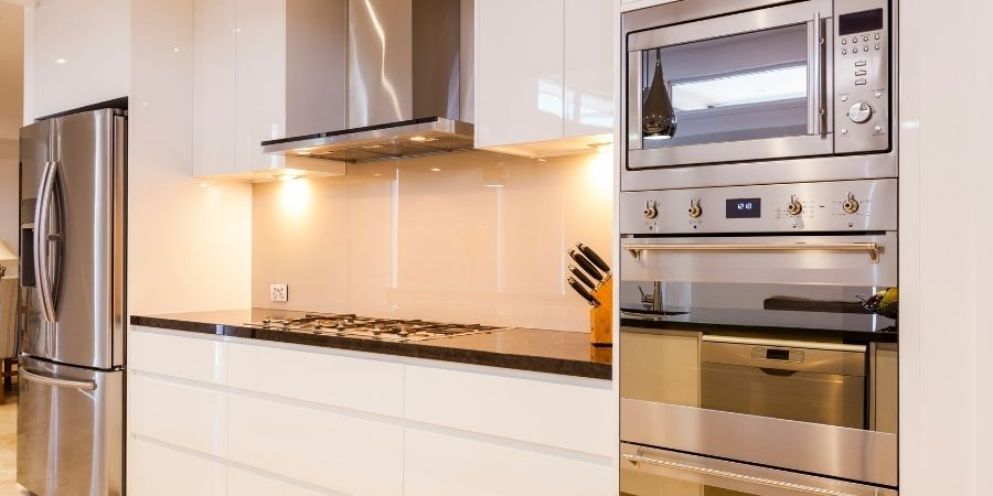luxurious high end stainless steel appliances in bright white kitchen