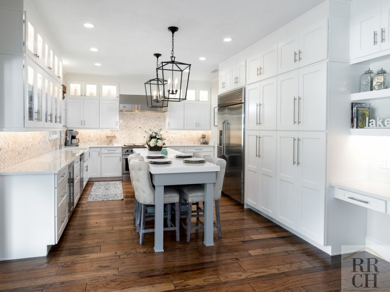 White Kitchen with Unique Lighting Fixtures Designed by Robinson Renovation & Custom Homes in Florida